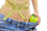 Woman's fit belly with measuring tape,apple and oversized jeans, isolated on white — Stock Photo