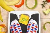 Feet on bathroom scale with Eat Healthy text fruit peals around — Stock Photo