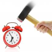 Hand holding hammer and red alarm clock,isolated on white — Stock Photo