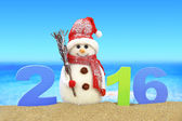 New year number 2016 and snowman on the beach — Stock Photo