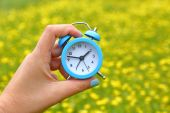 Hand holding an alarm clock with abstract nature background — Stock Photo