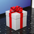 Gift box with red ribbon on black laptop keyboard — Stock Photo #77850014