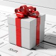 Gift box with red ribbon on white laptop keyboard — Stock Photo #77850568