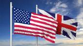 Waving flags of USA and UK on flagpole, on blue sky background. — Stock Photo