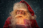 Santa Claus opening xmas present — Stock Photo