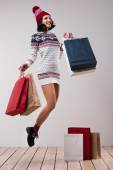 Woman jumping with shopping bags — Stock Photo