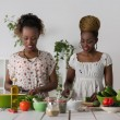 Two african women cooking salad — Stock Photo #65007861