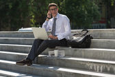 Man with laptop calling by phone — Stock Photo