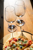Wineglasses and fresh baked pizza — Stock Photo