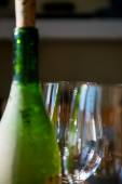 Wineglasses and green bottle of wine — Stock Photo