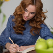 Woman writing in notepad — Stock Photo #70728905