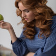 Woman eating apple while working — Stock Photo #70728915