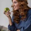 Woman eating apple while working — Stock Photo #70728919