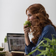Woman eating apple while working — Stock Photo #70728937