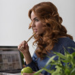 Woman eating apple while working — Stock Photo #70728947