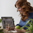 Woman eating apple while working — Stock Photo #70728951