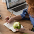 Woman eating apple while working — Stock Photo #70728965