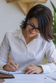 Woman writing at office — Stock Photo