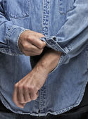 Man in denim shirt rolling up his sleeves — Stock Photo