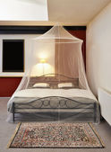 Cosi vintage bed with mosquito Net in a restored loft — Stock Photo