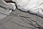 Disheveled sheets and pillows of an unmade bed — Stock Photo