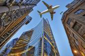 A jet plane flying over the city — Stock Photo