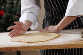 Chef sdjusting and flatten the dough — Stock Photo