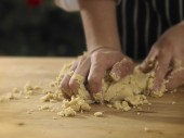 Kneading dough on table — Stock Photo
