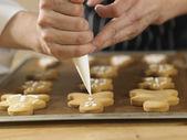 Chef decorating cookies — Stock Photo