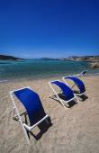 Deck chairs on the beach in a windy day — Stock Photo