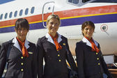 Flight assistants near an airplane — Stock Photo
