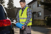 Man pouring fuel into gas tank of his car from blue gas canister — Stock Photo