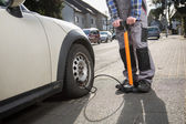 Pumping up a car tire after a malfunction — Stock Photo