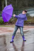 Wind blows the womans umbrella away — Stock Photo