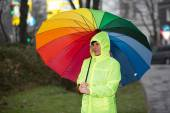 Rain protected woman waiting in the rain with her umbrella — Stock Photo