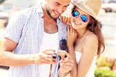 Joyful couple checking pictures on the camera — Fotografia Stock