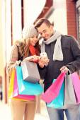 Happy couple shopping in the city with smartphone — Stock Photo