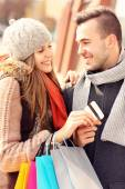 Young couple with credit card shopping in the city — Stockfoto