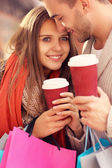 Happy couple with coffee shopping in the mall — Stock Photo