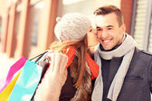 Happy woman kissing a man while shopping — Stock Photo
