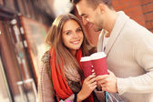 Joyful couple with coffee shopping in the mall — Stockfoto