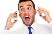 Furious businessman talking on two phones — Stockfoto