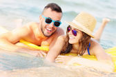 Young couple swimming on a matress — Stock Photo