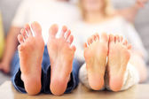 Barefeet of a happy couple lying on a sofa — Stock Photo