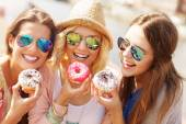 Group of friends eating donuts — Stock Photo