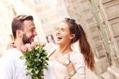 Joyful romantic couple with flowers — Stock Photo