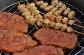 Delicious barbecue skewers and grill steaks on a grill — Stock Photo