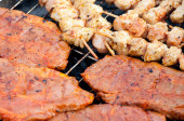 Hearty barbecue skewers and grill steaks on a grill — Stock Photo