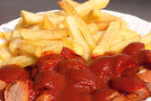 Berlin curry sausage with fries - Berliner Curry-Wurst mit Pommes — Stock Photo