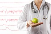 Female doctor's hand holding green apple. Close up shot on blurred medical background. Concept of Healthcare And Medicine. Copy space — Stock Photo